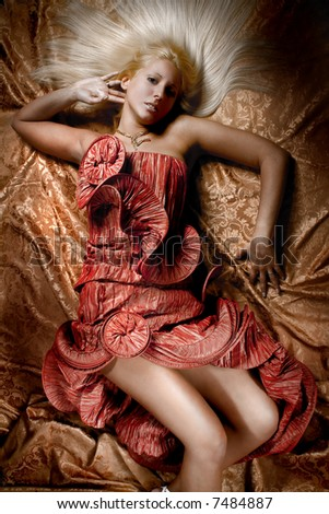 bride lying down in red wedding dress, studio shot - stock photo
