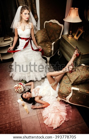Bride Lying on His Back with his Legs Up in the Glamorous Interior, the Second Bride Standing Beside. Both Brides Have Faces Like Dolls - Without Emotions - stock photo
