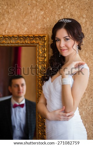 Bride next to the mirror in the mirror groom - stock photo