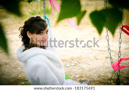 Bride on a swing in the park