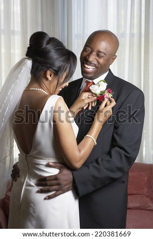 Bride pinning flowers onto groom's lapel - stock photo
