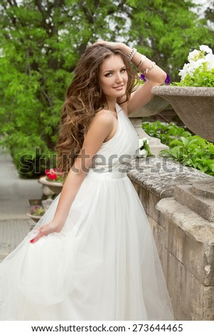 Bride Portrait Beautiful girl with long wavy hair in white wedding dress at park, outdoor. - stock photo