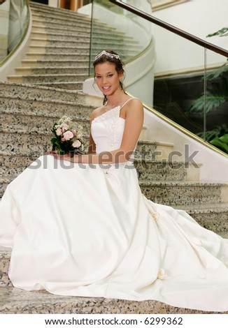 bride posing with wedding bouquet at the stairs