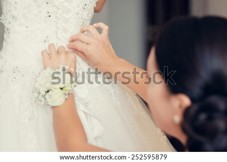 Bride preparations, while putting a dress on - stock photo
