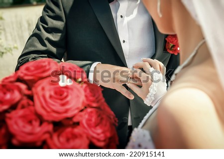Bride put on wedding ring on groom's hand on wedding ceremony. Focused on ring - stock photo