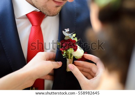bride puts beautiful buttonhole on jacket of her fiance