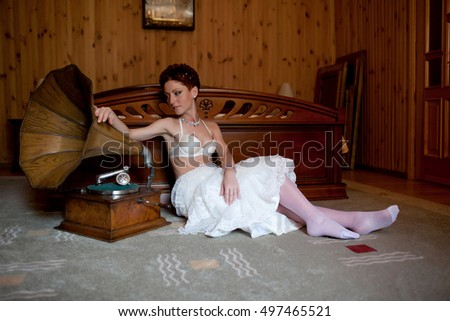 Bride puts her hand on old gramophone while sitting on the floor