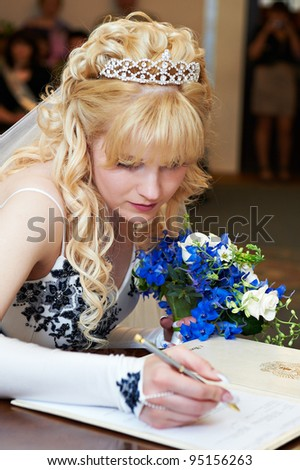 Bride puts signature on solemn registration of marriage in wedding palace - stock photo