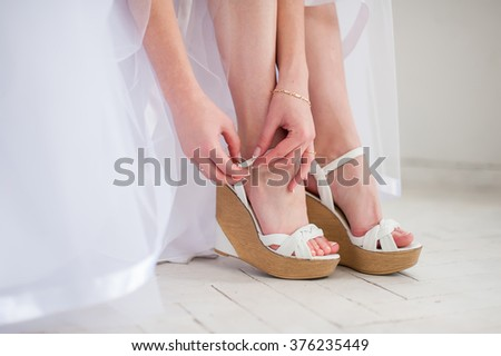 Bride puts White shoes for wedding - stock photo