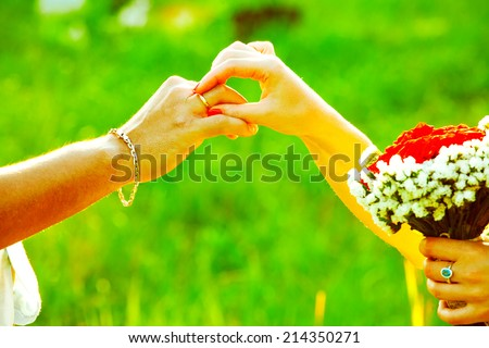 Bride putting a ring on groom's finger at outdoor wedding ceremony - stock photo