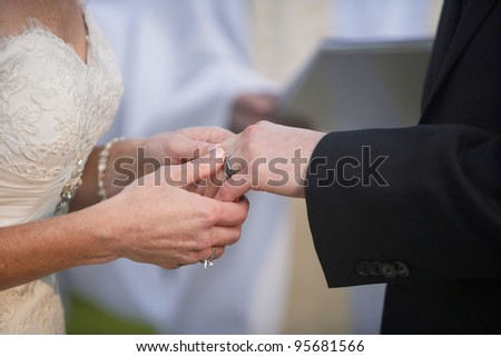 Bride putting a ring on groom's finger at wedding ceremony - stock photo