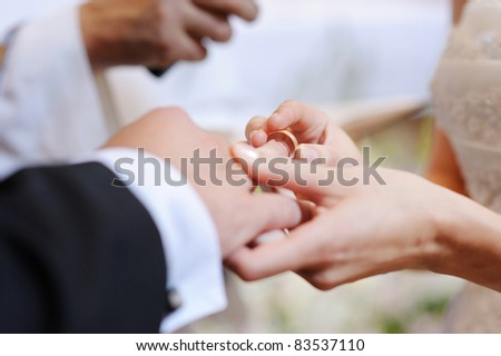 Bride putting a wedding ring on groom's finger - stock photo