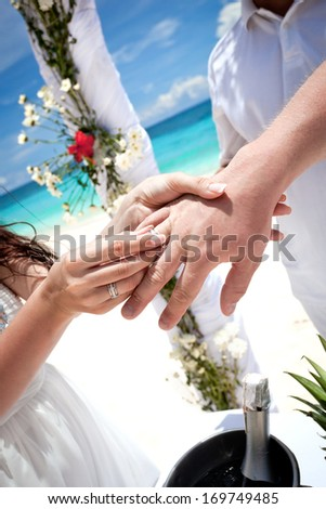 Bride putting a wedding ring on groom's finger, tropical wedding - stock photo