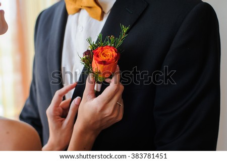 Bride putting on flower boutonniere on groom in black suit - stock photo