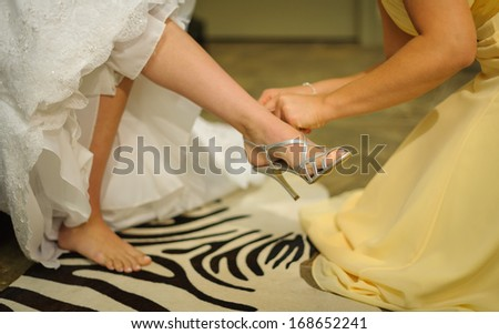 Bride putting shoes - stock photo