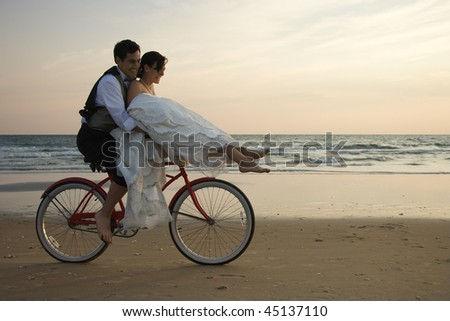 Bride rides the handle bars of a bicycle being driven by her groom on beach. Horizontal shot. - stock photo