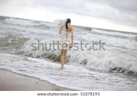 Bride running along sea coast in the wedding dress - stock photo