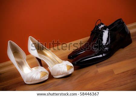 Bride's and groom's shoes on the floor - stock photo