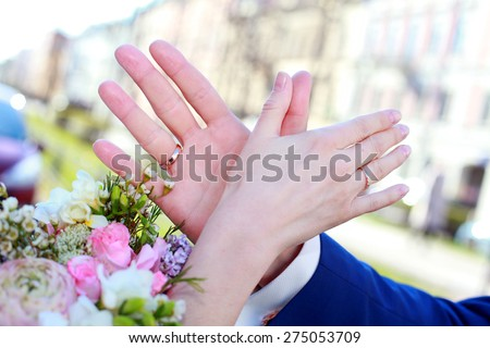bride's bouquet, hands and rings - stock photo