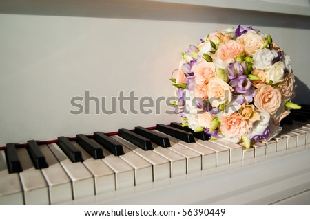 Bride's bouquet on a keys of white grand piano - stock photo