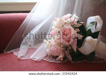 Bride's bouquet with details of veil. - stock photo