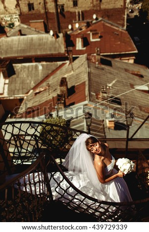 Bride's dress lies on the spiral stairs while she enjoys sunshine - stock photo