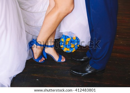 bride's feet in blue sandals and a groom wedding shoes. Wedding bouquet of blue and yellow flowers - stock photo