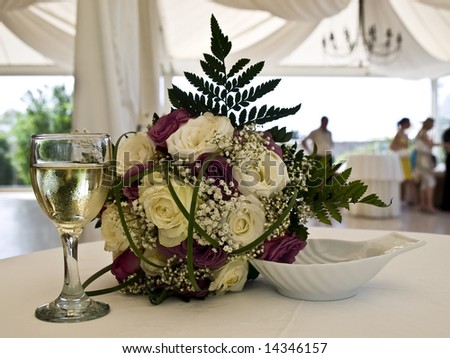 Bride's flower bouquet on table next to glass of wine