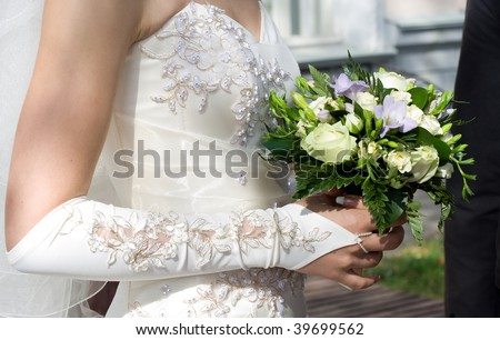 bride's hand holding bunch of flowers