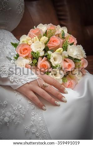 bride's hand holding wedding bouquet - stock photo