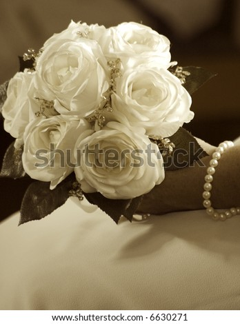 Bride's hand holding wedding bouquet, sepia toned