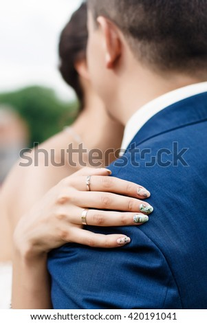 Bride's hand on the shoulder of the groom. bride Manicure. the groom's ear Rings on the fingers of the bride and beautiful manicure  - stock photo