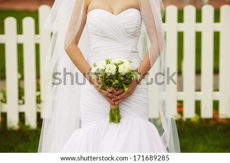Bride's hands with wedding bouquet of beige flowers over white wooden fence and green lawn. Trendy dress with vapory veil. Country (vintage) style. Close up. Copy-space. Outdoor shot - stock photo