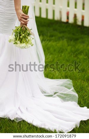 Bride's hands with wedding bouquet of beige flowers over white wooden fence and green lawn. Trendy dress with vapory veil. Country (vintage) style. Copy-space. Outdoor shot - stock photo