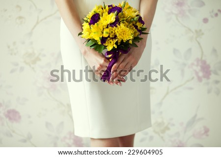 Bride's hands with wedding bouquet of violet and yellow flowers over stylish white dress. Vintage style. Close up. Copy-space. Indoor shot - stock photo