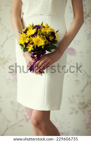 Bride's hands with wedding bouquet of violet and yellow flowers over stylish white dress. Vintage style. Close up. Indoor shot - stock photo