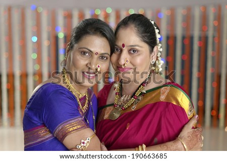 Bride's mother and Groom's mother greeting each other in Indian Hindu Wedding ceremony. - stock photo