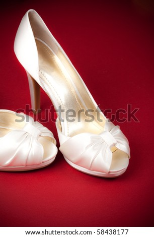 Bride's shoes on red background - stock photo