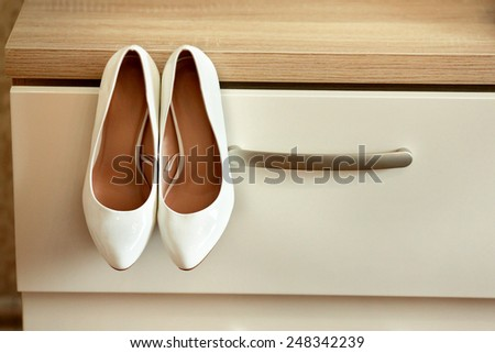 Bride's shoes on the chest of drawers - stock photo