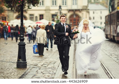 Bride screams while running along the tramways with a groom