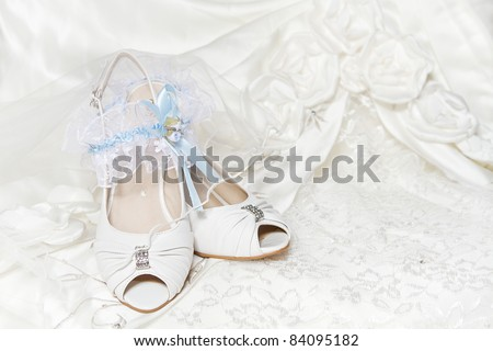 Bride shoes garter, with blue ribbon, wedding dress. Closeup of wedding accessories. - stock photo