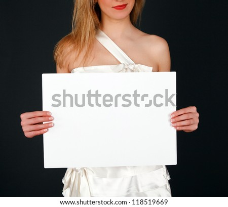 Bride shows white board with copyspace, black background - stock photo