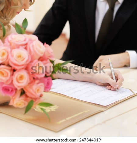 Bride signing marriage license or wedding contract - stock photo