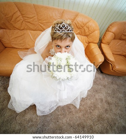 Bride sits on a brown leathern sofa - stock photo
