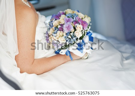 bride sitting in wedding car, holding bouquet of various flowers