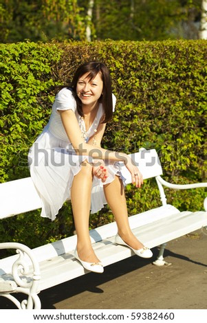 Bride sitting on a bench - stock photo