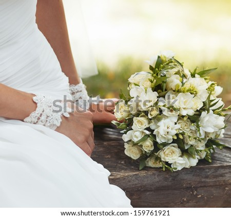 Bride sitting on bench holding wedding bouquet of various flowers. - stock photo