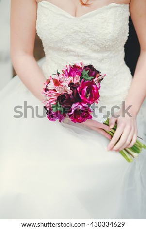 Bride sitting on bench holding wedding bouquet of various flowers.