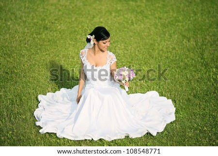 bride sitting on grass in park - stock photo