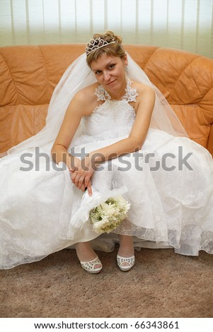 Bride sitting on sofa waiting for ceremony - stock photo
